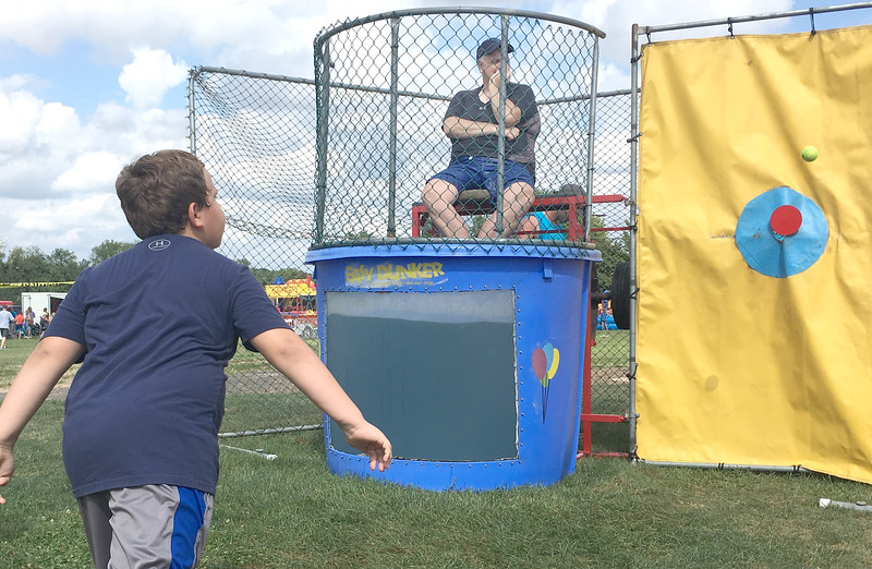Lower Makefield Supervisor John Lewis watches as a ball just misses the mark at the dunk tank.