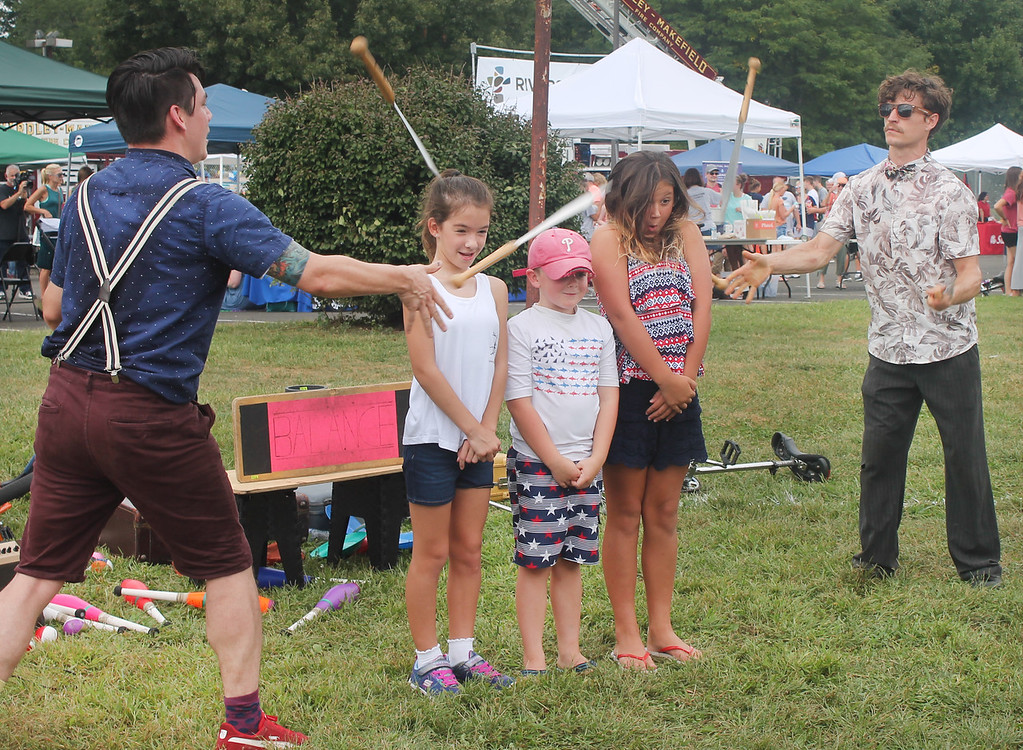 . Yikes! Three young volunteers stand very still as members of Patchwork Circus juggle knives on either side of the kids.