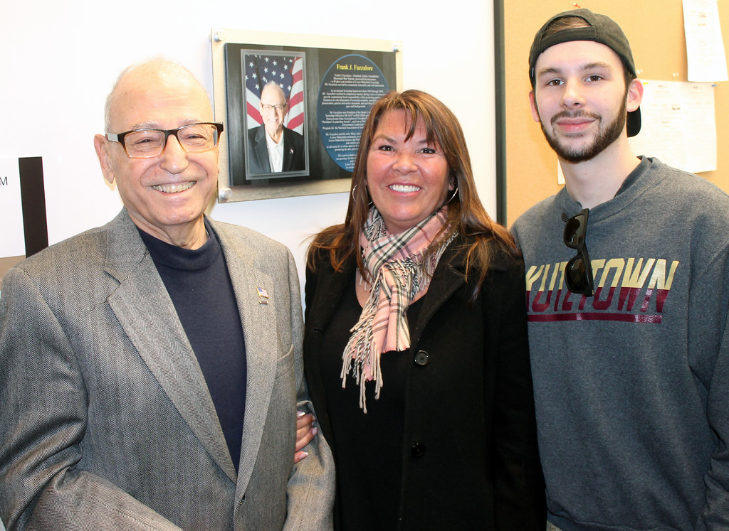 . Frank Fazzalore with his daughter, Jamie Fazzalore-Truelove, and his grandson next to a wall plaque recognizing Frank\'s many contributions to the community.