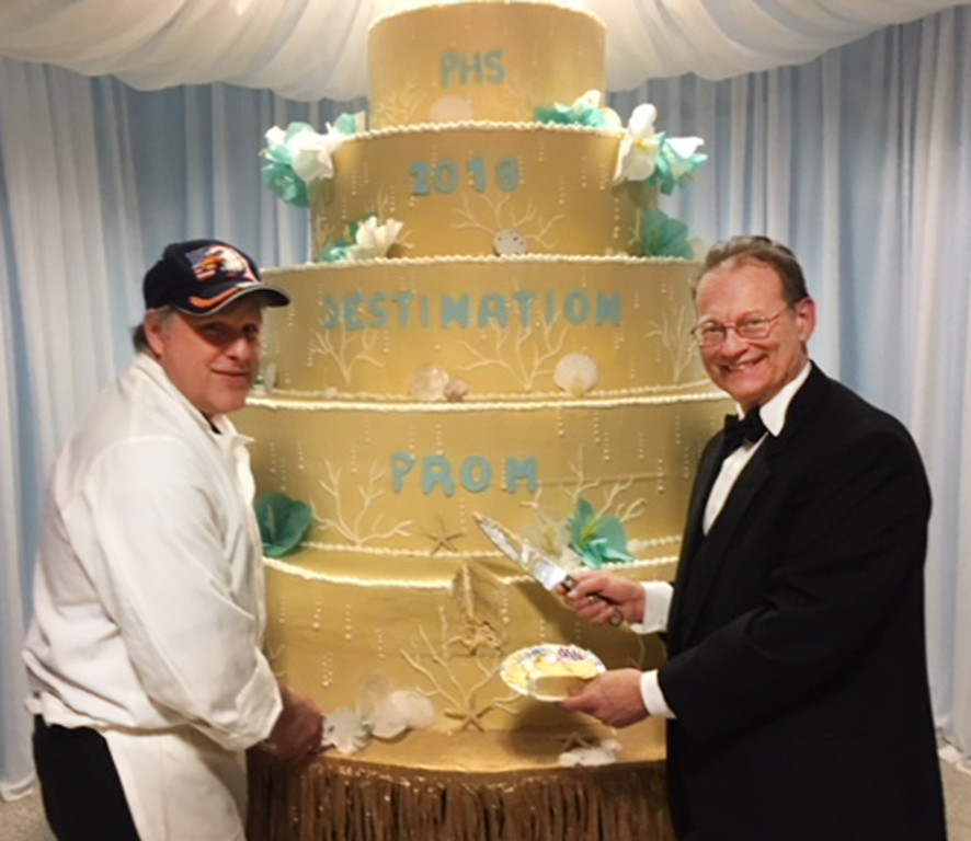 . The Prom\'s senior advisor Tony Napoli cuts the Destination Prom Cake with Piazza�s Bakery owner John Hose. Each attendee received a boxed piece of freshly baked 2018 prom cake upon leaving. The baker (Piazza�s Bakery) created mini versions of the large cake displayed at the prom and cut them into pieces to be boxed and given as favors.