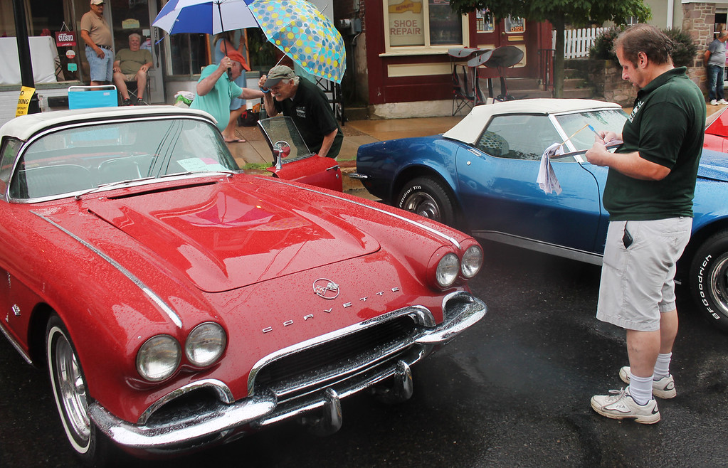 . Show judge Fred Fletcher makes notes as he checks out this red 1962 Chevrolet Corvette owned by Michael Gaffney.