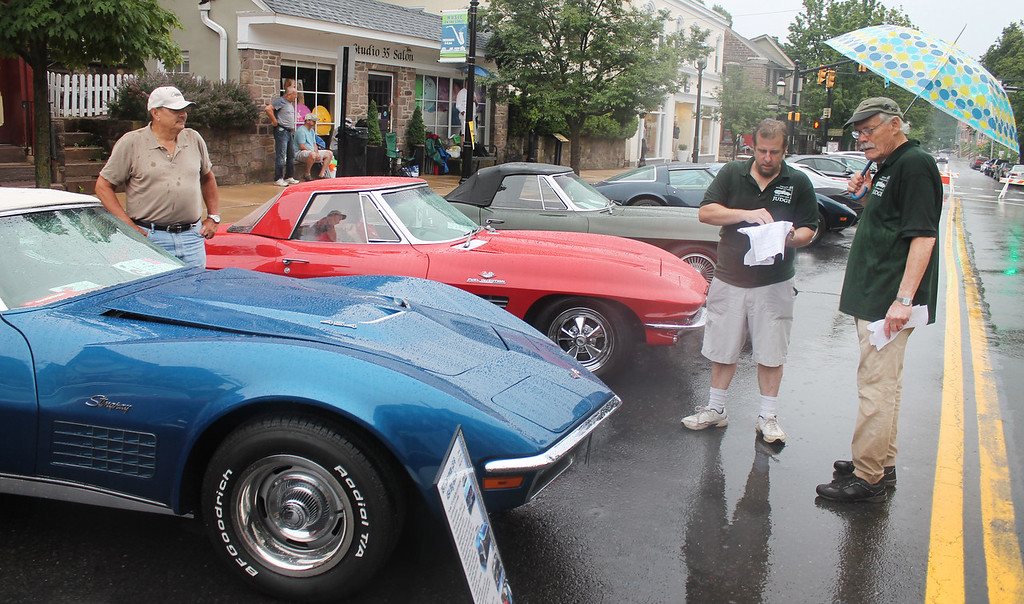 . Judges Charlie Lewis and Fred Fletcher inspect the Corvettes.