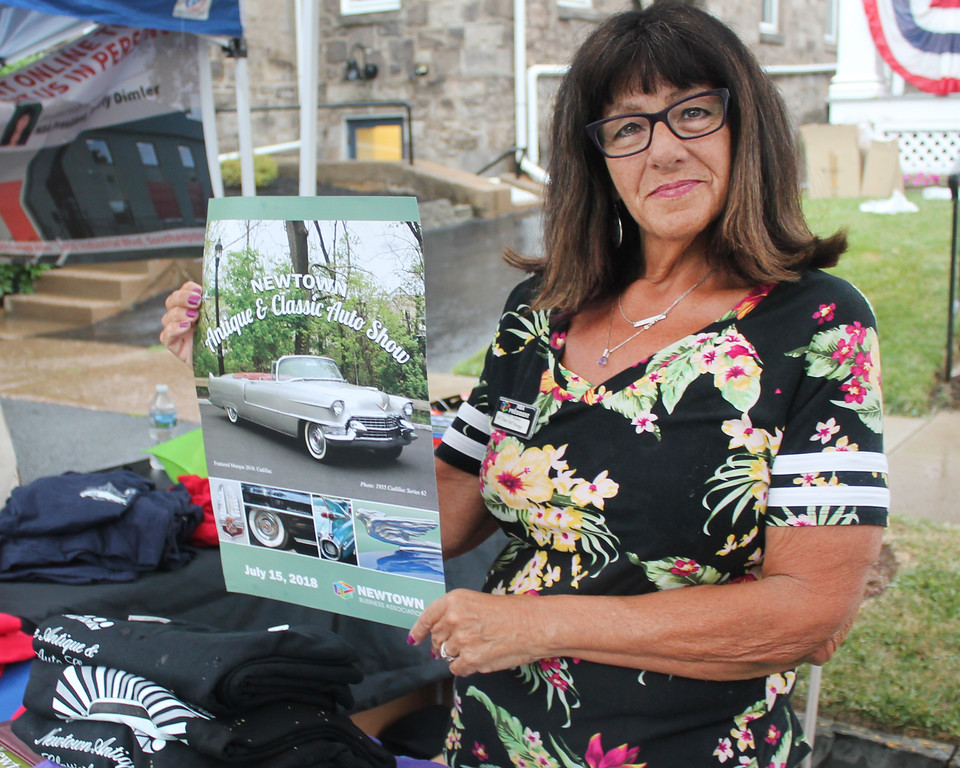 . Newtown Business Association President Beverly Dimler shows off this year\'s Antique & Classic Auto Show poster.