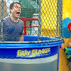 Lower Makefield Supervisor Jeff Benedetto falls into the drink after being dunked by the boy at the right.