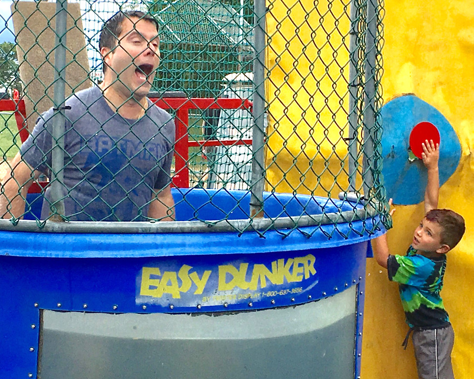 . Lower Makefield Supervisor Jeff Benedetto falls into the drink after being dunked by the boy at the right.