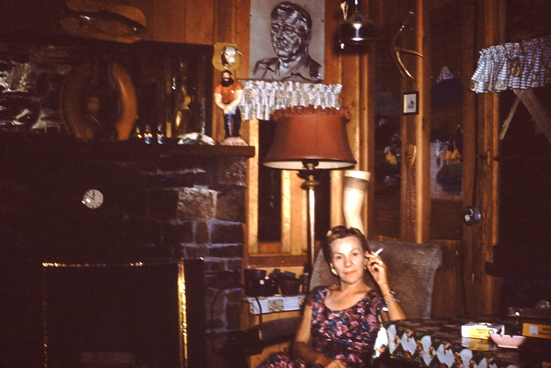 "Estelle Porter-Young - 1958 (Aug) - Married Bud Yaden on June 22, 1958 - Cabin on the Naches River - Cliffdell, WA - From the Byron W. Yaden 35MM Slide Collection<br /> <br /> Note from Brother David:<br /> <br /> Memories indeed! I remember most of these artifacts in the picture--the stockinged leg, the toilet seat picture frame--this place was packed!  Where did all this stuff end up?  And everybody smoked--all the old aunts-Gert, Paula, Min, Grampa had his pipe--no worries about 2nd hand smoke then!  And even to this day, I don't know where everyone stayed--most of the time our family slept outside on a mattress--don't ask me where the aunts stayed unless it was in the small guest house nearby. <br />  <br /> One morning I turned on the kitchen faucet and a small minnow came out!  Fish for breakfast!  Here I dug many a hole for the honeypot--always sloshed on my socks on the way to emptying it. <br />  <br /> Truly a wonderful place to wile away the hours and days. I loved being there.<br /> <br /> <br /> Counter note from Sister Pauli:<br /> <br /> My most vivid memories are of the freeway of ""cobwebs"" that encircled<br /> the crib I used to have to sleep in!  No wonder I have issues...<br /> <br /> Brother Dan:<br /> <br /> Gee, Pauli's memories seem to have a little different slant to them.....did you feed her that minnow, David?<br /> <br /> Brother David:<br /> <br /> What's a tiny minnow among siblings?! It went down easy."