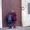 Couple peering through a huge metal door in Prague, Czech Republic in February 2014