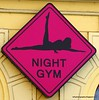 Night gym sign with a sexy woman legs akimbo for a strip club in Prague, Czech Republic in February 2014
