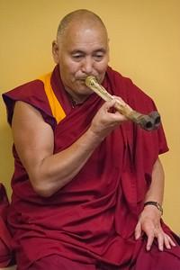 Lama Sangye Monlam testing a musical instrument