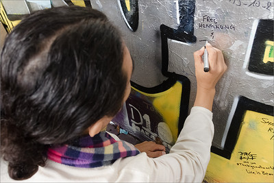 Jhola Techung writing message on Lennon wall in Prague 2014