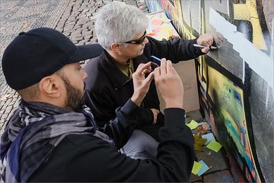 Michel Tyabji writing message on Lennon wall in Prague