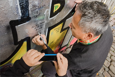 Rinzing Wangyal writing message on Lennon wall in Prague