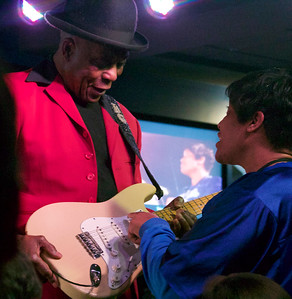 """Buddy Guy gets a fan to """"help"""" out."""