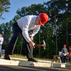 Chancellor Randy Woodson swings a hammer prior to the Build-A-Block Habitat for Humanity project ceremony.