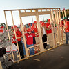 Chancellor Randy Woodson and other NC State participants and volunteers raise wall during the Build-A-Block Habitat for Humanity project ceremony.