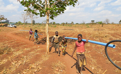 When reaching a village, everyone pitches in to carry pipes and pump parts down to the well site.
