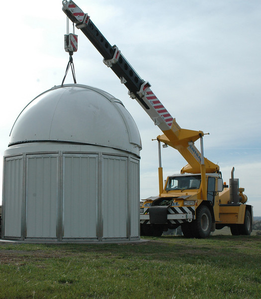 On goes the prefabricated dome roof. On a low wall in a sheltered site, a football team of mates can lift the dome into place, but not way over head-height with the wind gusting 36 KPH. Tip: Clean the grease on the dome track from time to time or it sets like toffee.