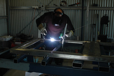 Darth Vader constructing a wall panel. The twelve structural panels are made from 100x50x3 stainless steel. No rust, no painting. Ever. The power hacksaw at right rear went through twelve blades.