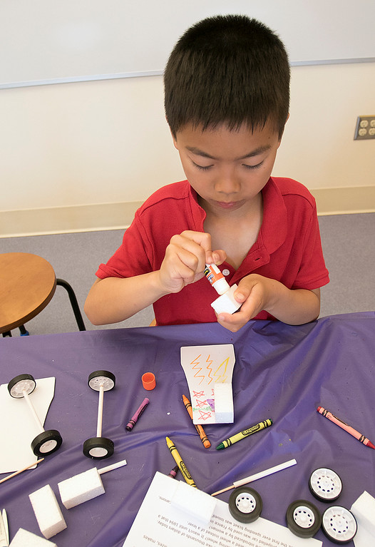 . Kids put together some cars during a program at the Leominster Public Library on July 17, 2019. Ethan Lao, 7, of Sterling works on putting his car together at the program. SENTINEL & ENTERPRISE/JOHN LOVE