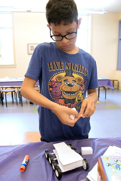 . Kids put together some cars during a program at the Leominster Public Library on July 17, 2019. Johnny Vicioso, 11, of Leominster looks over the car he was building and wonder what to do next during the program. SENTINEL & ENTERPRISE/JOHN LOVE