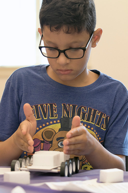 . Kids put together some cars during a program at the Leominster Public Library on July 17, 2019. Johnny Vicioso, 11, of Leominster works on putting his car together at the program. SENTINEL & ENTERPRISE/JOHN LOVE