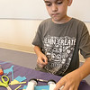 Kids put together some cars during a program at the Leominster Public Library on July 17, 2019. Luca Puglisi, 11, of Leominster works on the design of his car at the program. SENTINEL & ENTERPRISE/JOHN LOVE
