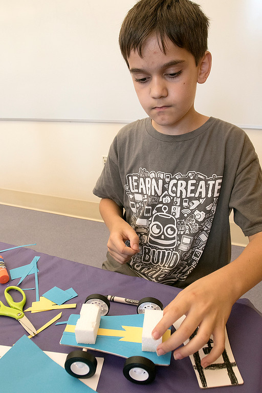 . Kids put together some cars during a program at the Leominster Public Library on July 17, 2019. Luca Puglisi, 11, of Leominster works on the design of his car at the program. SENTINEL & ENTERPRISE/JOHN LOVE
