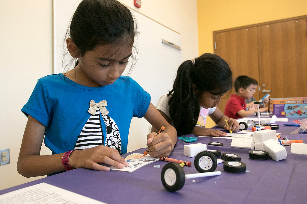 . Kids put together some cars during a program at the Leominster Public Library on July 17, 2019. Amaya Woods, 8, of Fitchburg decorates her car before putting it together. SENTINEL & ENTERPRISE/JOHN LOVE