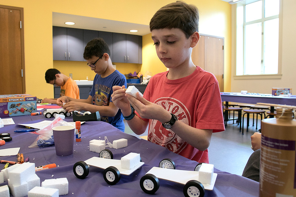 . Kids put together some cars during a program at the Leominster Public Library on July 17, 2019. Benjamin Dill, 12, of Leominster works on putting his car together during the program. SENTINEL & ENTERPRISE/JOHN LOVE