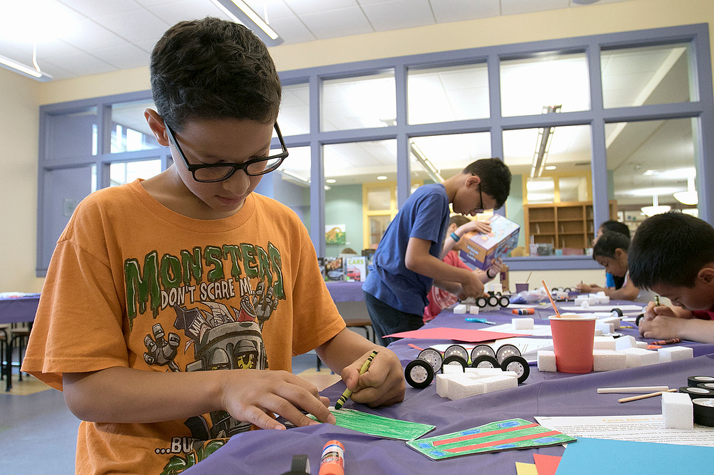 . Kids put together some cars during a program at the Leominster Public Library on July 17, 2019. Nico Vicioso, 11, of Leominster works on putting his car together at the program. SENTINEL & ENTERPRISE/JOHN LOVE