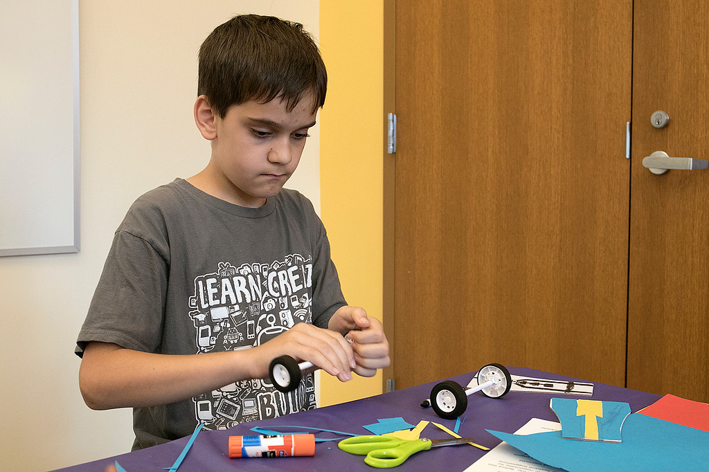 . Kids put together some cars during a program at the Leominster Public Library on July 17, 2019. Luca Puglisi, 11, of Leominster works on putting his cars wheels together at the program. SENTINEL & ENTERPRISE/JOHN LOVE