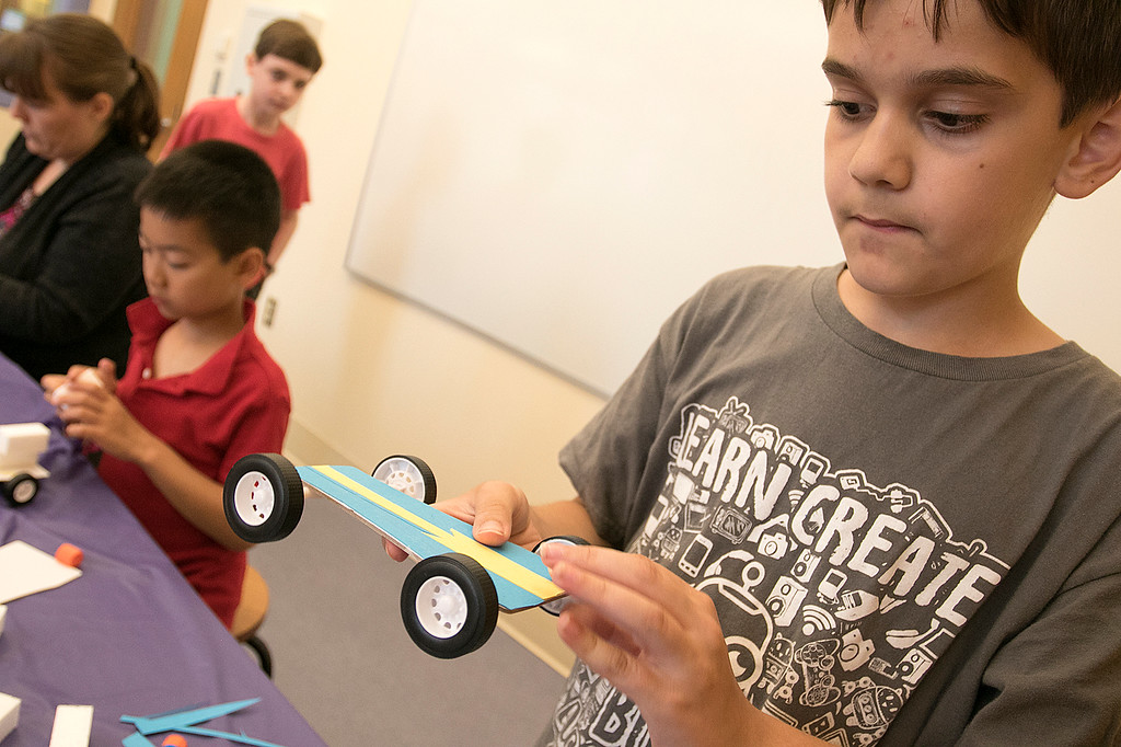 . Kids put together some cars during a program at the Leominster Public Library on July 17, 2019. Luca Puglisi, 11, from Leominster looks over the car he built during the program. SENTINEL & ENTERPRISE/JOHN LOVE