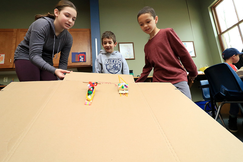 Lunenburg Public Library's Saturday STEM program created an engineering challenge too try and build a dog sled that they raced down a ramp to see how well it was built. The idea was to build it with popsicles sticks, tape, straws, scissors and pipe cleaners. They were to build it so that it could hold small pom poms. Matthew, center, and Jeriel Plaza, 8, watch as Abby Shapiro the volunteer for the Saturday STEM program starts the race between their two sleds. SENTINEL & ENTERPRISE/JOHN LOVE