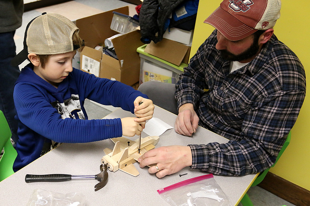 . Garrett Davis, 6, and his dad Steve Davis of Ashburnham work on building and painting a wooded plane at a program put on by Robert Leduc of Wooden Toys and Crafts at the Stevens Memorial Library in Ashburnham. SENTINEL & ENTERPRISE/JOHN LOVE