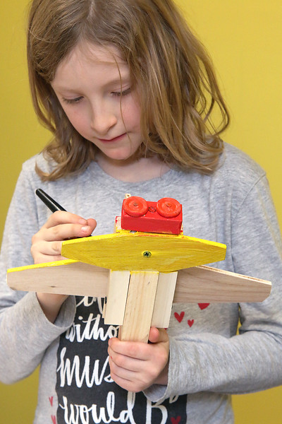 Brynn Saltsman, 8, of Ashburnham works on building and painting a wooded plane at a program put on by instructor Robert Leduc of Wooden Toys and Crafts at the Stevens Memorial Library in Ashburnham. SENTINEL & ENTERPRISE/JOHN LOVE