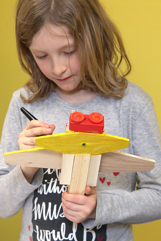 . Brynn Saltsman, 8, of Ashburnham works on building and painting a wooded plane at a program put on by instructor Robert Leduc of Wooden Toys and Crafts at the Stevens Memorial Library in Ashburnham. SENTINEL & ENTERPRISE/JOHN LOVE