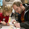 Octavia Feeley, 5, and her dad Corey Feeley of Westminster work on building and painting a wooded plane at a program put on by Robert Leduc of Wooden Toys and Crafts at the Stevens Memorial Library in Ashburnham. SENTINEL & ENTERPRISE/JOHN LOVE