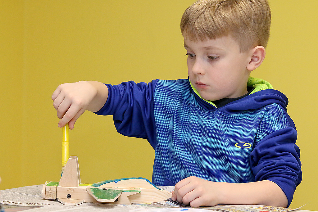 . Chase McGillibary, 5, works on building and painting a wooded plane at a program put on by instructor Robert Leduc of Wooden Toys and Crafts at the Stevens Memorial Library in Ashburnham. SENTINEL & ENTERPRISE/JOHN LOVE