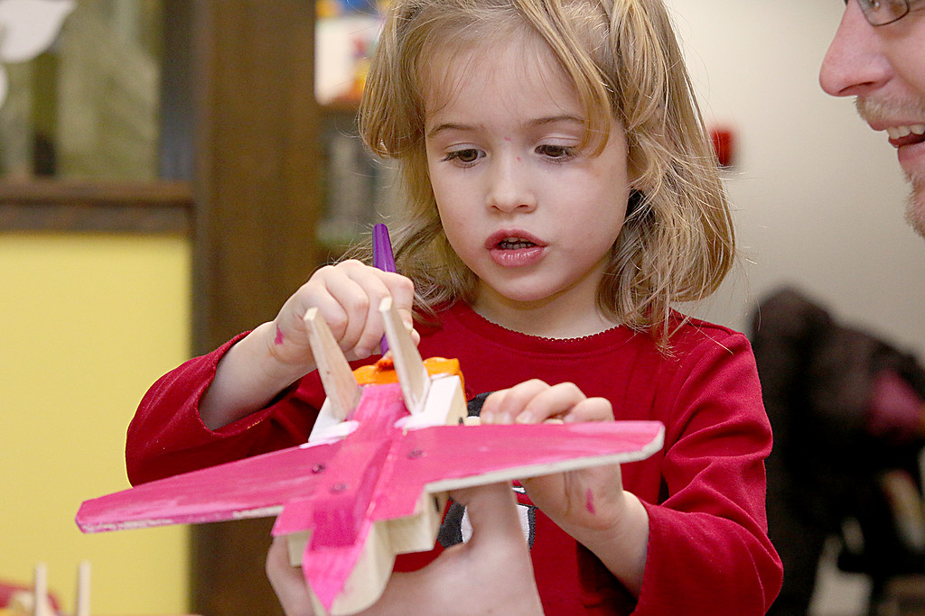 . Octavia Feeley, 5, and her dad Corey Feeley of Westminster work on building and painting a wooded plane at a program put on by Robert Leduc of Wooden Toys and Crafts at the Stevens Memorial Library in Ashburnham. SENTINEL & ENTERPRISE/JOHN LOVE