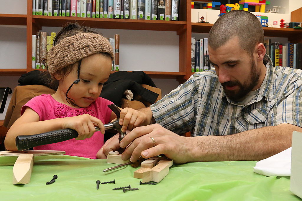 . Liberty Rood, 3, and her dad Mark Rood work on building and painting a wooded plane at a program put on by Robert Leduc of Wooden Toys and Crafts at the Stevens Memorial Library in Ashburnham. SENTINEL & ENTERPRISE/JOHN LOVE