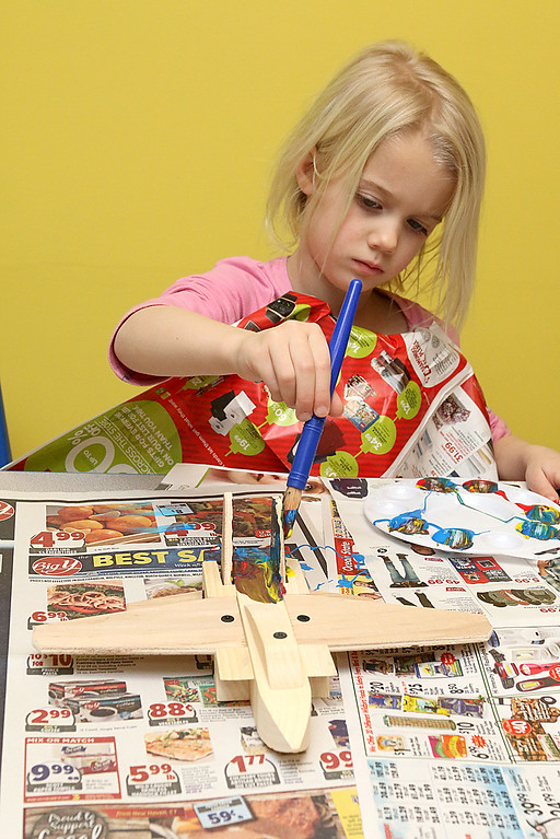 . Alysa Wood, 4, of Winchendon works on building and painting a wooded plane at a program put on by instructor Robert Leduc of Wooden Toys and Crafts at the Stevens Memorial Library in Ashburnham. SENTINEL & ENTERPRISE/JOHN LOVE