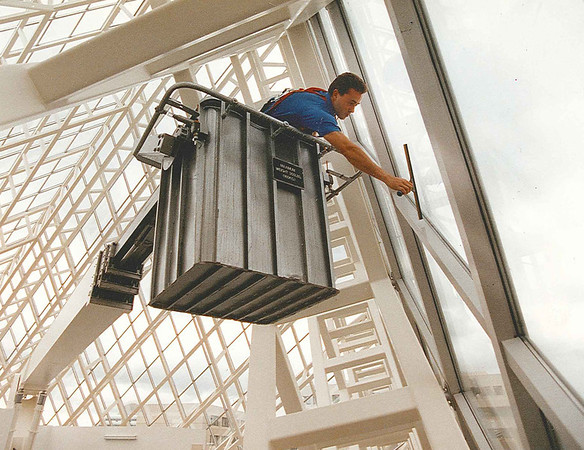 Mark Cale of focus building services demonstrated the way to clean pyramid style windows at city hall on Wednesday July 22/93