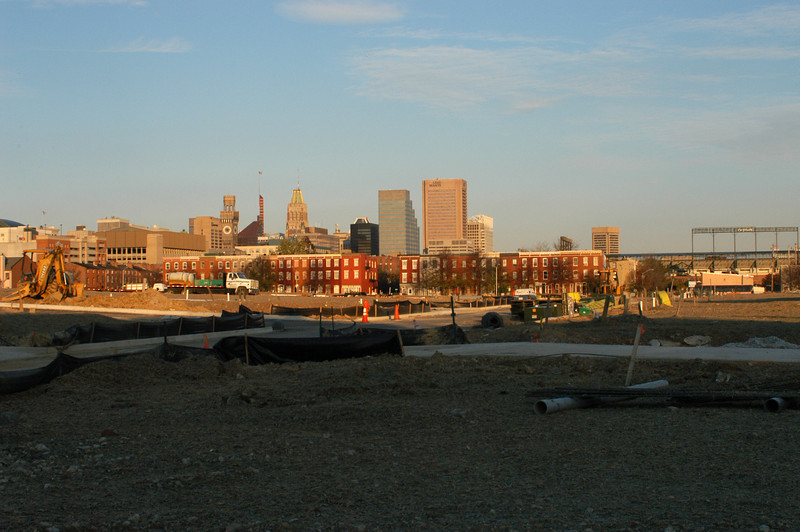 Skyline, rowhouse neighborhood, and new institutional construction in West Baltimore.