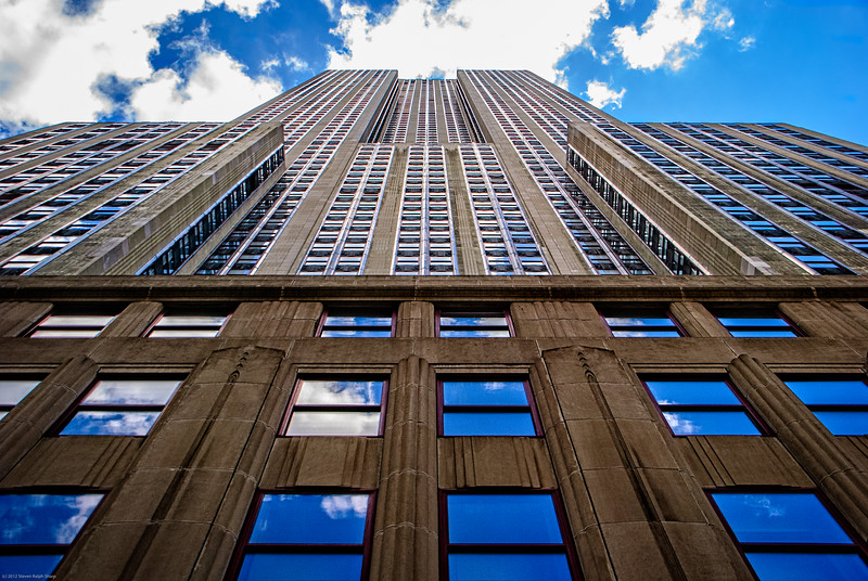 "A view of the Empire State Building from the ground. Aaron Barlow, his son Sam and I had just finished taking a tour of the Empire State Building and were walking to the next site to see. Aaron looked up and said, ""Wow, that's quite a site"". So I looked where he was looking and this is what I saw."