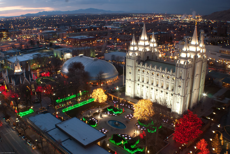 This is a view of Temple Square at Christmas-time from the Founders Room on the 18th Floor of the Zions Bank Building where I work. After publishing this picture, someone said that the big tree with the red lights in the lower right of the picture is a Cedar of Lebanon and that it is only lit up every other year.<br /> The sun had just set and the western sky was still a bit blue. I love all the colors in this shot. I put the wide angle attachment on the lens to capture as much of Temple Square as I could.