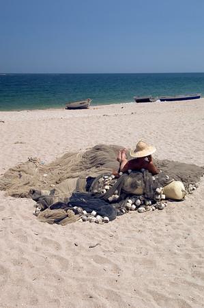 Europe, Romania, Black Sea Coast, Vama Veche fishing village and beach, fisherman resting on fishing nets