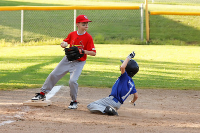 Wyatt Pfeiffer slides for third base while Connor McCool snags the force out and looks to turn two with the bases loaded in the 7-8 year-old Saxonburg little league championship game. Mcool's Cardinals topped the Cubs 13-4.  (Wyatt Pfeiffer also pictured) Seb Foltz/Butler Eagle