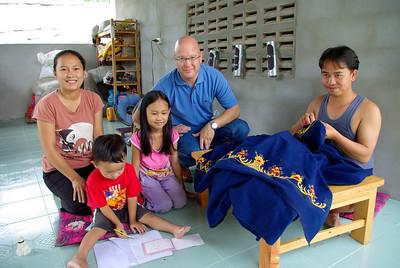 Hele familien er samlet. Far broderer damebunad mens mor hjelper barna med lekser.