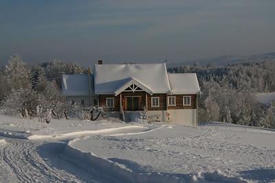 Vinterbilde av driftsbygningen og bunadsloftet.