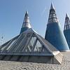 Dachgarten der Bundeskunsthalle mit sorgfältig ausgewählter Architektur. Durch die Basis der transparenten Pyramide hindurch ist im Hintergrund die Wildblumenwiese zu sehen.